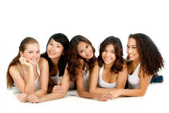 Diverse Teenagers. A group of teenagers with diverse ethnicities lying down against white background Royalty Free Stock Images