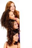 Diverse Teenagers with Blank Sign. A group of teenagers with diverse ethnicities looking at a blank space against white background Royalty Free Stock Photography