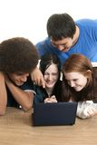 Diverse teens with laptop. Four teenagers of various ethnic backgrounds smile and laugh while looking at a laptop computer together Royalty Free Stock Photo