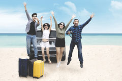 Diverse tourists look joy on the beach. Portrait of diverse tourists looks joy while jumping with a suitcase and a car on the beach Royalty Free Stock Photos