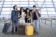 Diverse travelers looking at something at the airport Stock Photography