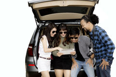 Diverse travelers with a tablet behind the car Royalty Free Stock Images