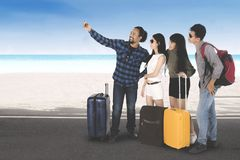 Diverse travelers taking pictures on the beach Stock Photo
