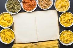 Diverse types van Italiaanse deegwaren en leeg kookboek stock afbeelding