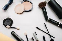 Diverse vastgestelde make-upproducten: borstels, oogschaduw, poeder, mascara, schoonheidsmiddelen op lichte witte achtergrond wor stock afbeeldingen