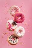 Diverse verfraaide doughnuts in motie die op roze achtergrond vallen stock afbeeldingen