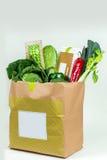 Diverse verse greens, groenten en wit vakje in document zak Stock Foto's