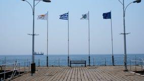 Diverse vlaggen die in de wind in de ochtend op de pijler in de oude Griekse stad van Limassol fladderen stock footage