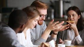 Diverse vrienden die delend pizza die interessant nieuws bespreken tijdens ontmoetingsplaats spreken stock footage