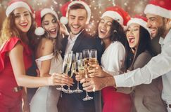 Diverse vrienden die met champagneglazen clinking op Nieuwjaar` s Vooravond stock foto's