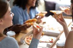 Diverse vrienden die van tijd genieten die samen pizza eten stock afbeelding