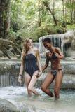 Diverse women couple enjoying the waterfall stock photography