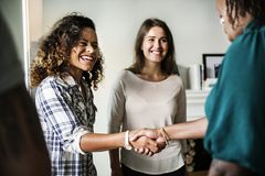 Diverse women shaking hands smiling Stock Images