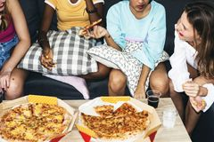 Diverse women sitting on the couch eating pizza together Stock Photos