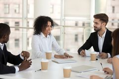 Diverse workers and coach during briefing in modern office. Biracial mixed race team leader presenting new business idea talking to diverse multiracial stock images
