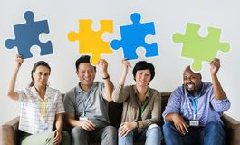 Diverse workers sitting and holding puzzle icons Stock Photo