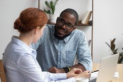 Diverse coworkers talking having pleasant conversation in office. Diverse workmates take break during workday talking have pleasant conversation feels amity royalty free stock photography