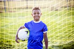 Diverse young boy on a youth soccer team. Standing in front of a soccer goal. Lots of copy space Stock Photos