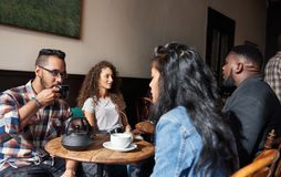 Diverse young friends hanging out together in a cafe stock photos