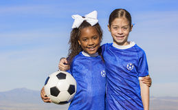Diverse young girl soccer players. Cute, young african american and hispanic girls soccer players holding a ball with a simple blue sky background. Lots of room Stock Images