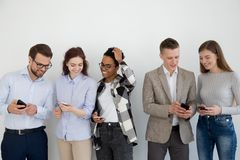 Diverse young people in queue communicate using smartphones stock photography