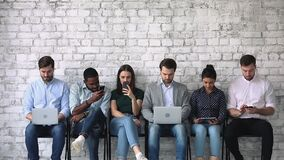 Diverse young people with gadgets, waiting for job interview.