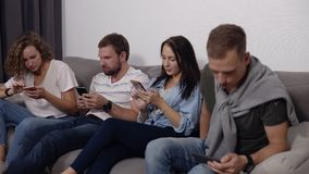 Diverse young people sitting in row on couch together obsessed with devices online, caucasian addicts using their. Smartphones, digital life and gadgets overuse stock footage