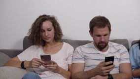 Diverse young people sitting in row on the grey couch together obsessed with devices online, caucasian addicts using. Their smartphones. White wall background stock video footage