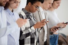 Diverse young people standing in row using smartphones. Close up of diverse young people stand in row near wall holding smartphones checking social media, group stock image