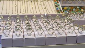 Diverse zilveren die ringen met edelstenen en Juwelen van zilver op het winkelvenster worden gemaakt stock video