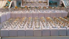 Diverse zilveren die ringen met edelstenen en Juwelen van zilver op het winkelvenster worden gemaakt stock footage