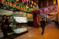 Diversehandeln säljer guld- smycken och håller ögonen på afton i Macao Arkivbild