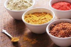 Diverses épices colorées sur la table en bois dans des cuvettes Ingrédients de nourriture et de cuisine Photos libres de droits