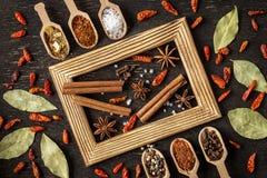 Diverses épices dans des cuillères en bois sur la table en pierre foncée images libres de droits