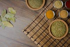 Diverses épices fraîches dans des cuvettes, fond en bois, vue supérieure photographie stock libre de droits