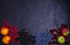 Diverses baies fraîches d'été Mélange des fruits et des baies sur le fond noir Bannière de fruit photographie stock libre de droits