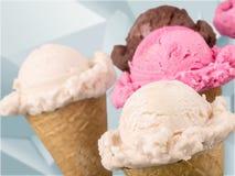Diverses boules de crème glacée dans des cônes de gaufre sur brouillé Photos stock