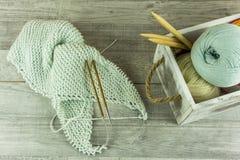 Diverses boules de laine de couleurs dans une boîte en bois avec des aiguilles de tricotage Image stock