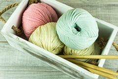 Diverses boules de laine de couleurs dans une boîte en bois avec des aiguilles de tricotage Photo stock