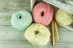 Diverses boules de laine de couleurs dans une boîte en bois avec des aiguilles de tricotage Images libres de droits