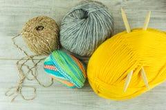Diverses boules de laine de couleurs dans une boîte en bois avec des aiguilles de tricotage Image libre de droits
