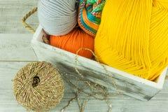 Diverses boules de laine de couleurs dans une boîte en bois avec des aiguilles de tricotage Photos stock