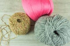 Diverses boules de laine de couleurs dans une boîte en bois avec des aiguilles de tricotage Photo libre de droits