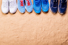 Diverses chaussures de sports dans une rangée contre le sable, tir de studio Photographie stock libre de droits