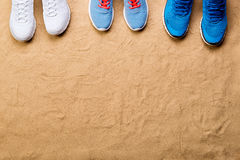 Diverses chaussures de sports dans une rangée contre le sable, tir de studio Photo stock