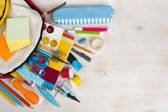Diverses fournitures de bureau d'école et de papeterie au-dessus de fond en bois de texture image libre de droits