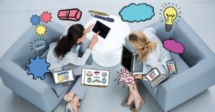 Diverses icônes au-dessus des femmes d'affaires à l'aide des ordinateurs portables sur le divan Photographie stock