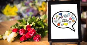 Diverses icônes sur le comprimé numérique par des fleurs sur la table Image libre de droits