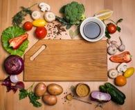Diverses légumes et épices et planche à découper vide coloré Image stock
