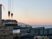 Diverses pièces de machines, poulies, équipement de expédition dans un secteur de dock avec le fond de San Francisco Bay photos stock